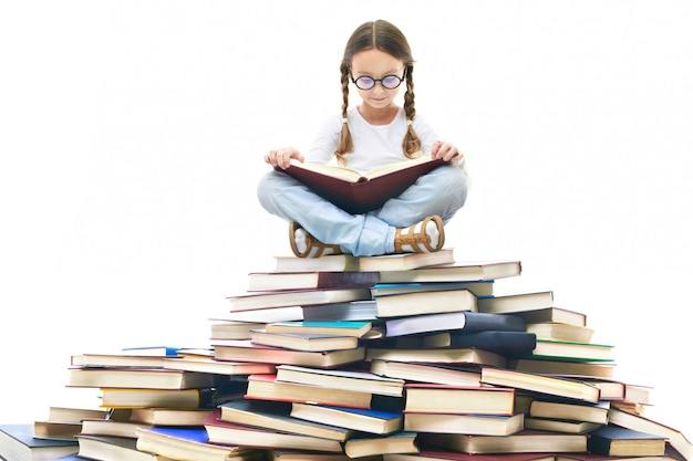 Fille concentré entouré de livres Photo gratuit