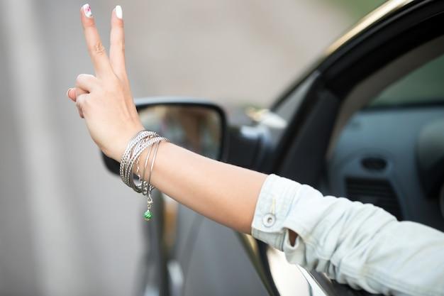 Fille de conduite et montrant le geste de la victoire Photo gratuit