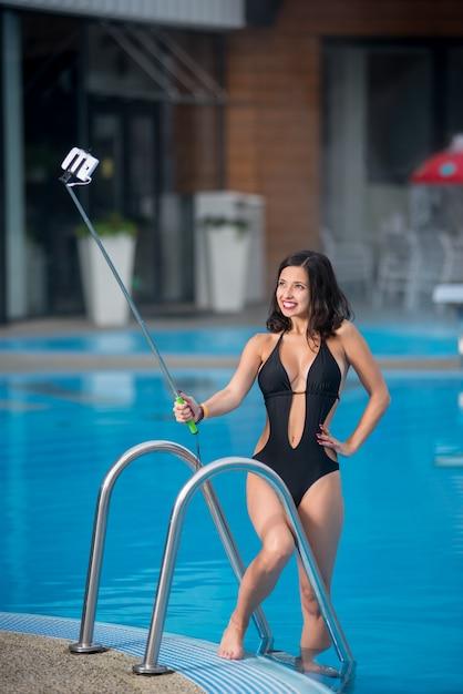 Fille contre piscine fait selfie photo Photo Premium
