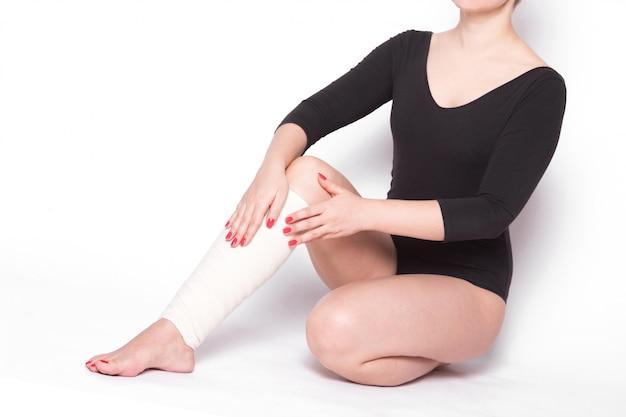 Fille corrige un bandage élastique qui cravate Photo Premium