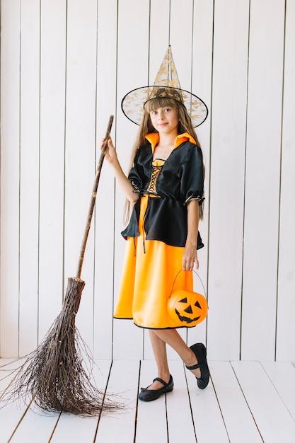 Fille en costume d'halloween avec balai qui pose en studio Photo gratuit