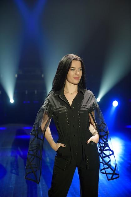 Fille En Costume Noir Sur Scène Avec Un Fond Bleu Clair Photo Premium