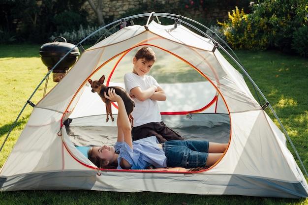 Fille couchée et jouant avec un chien devant son petit frère dans une tente Photo gratuit