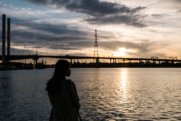 Fille coucher de soleil en mer et pont Photo gratuit