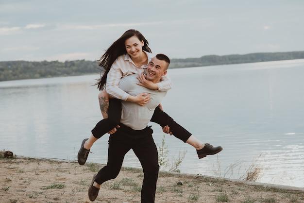 Fille De Couple Heureux Et Mec S'amusant Sur La Plage Au Bord De La Rivière En été. La Photo Est Floue En Raison Du Mouvement Et De La Vitesse D'obturation Courte Photo Premium