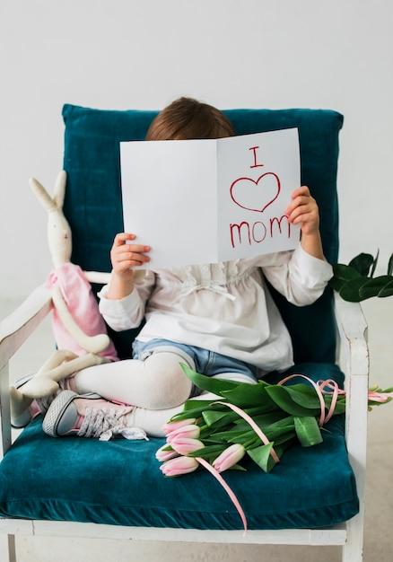 Fille couvrant le visage avec une carte de voeux avec l'inscription de ma maman Photo gratuit