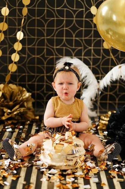Fille curieuse piquer un doigt dans son premier anniversaire smash gâteau. Photo gratuit