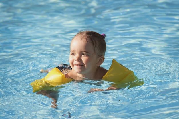Fille dans les accoudoirs pour nager en vacances dans la piscine. spa, cours de natation, vacances, traitement de l'eau Photo Premium