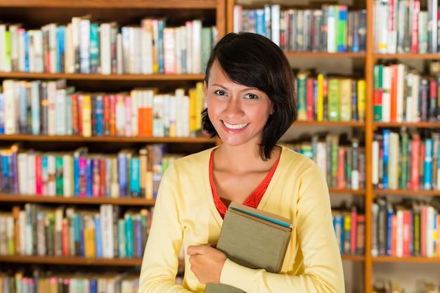 Fille dans la bibliothèque tenant un livre Photo Premium