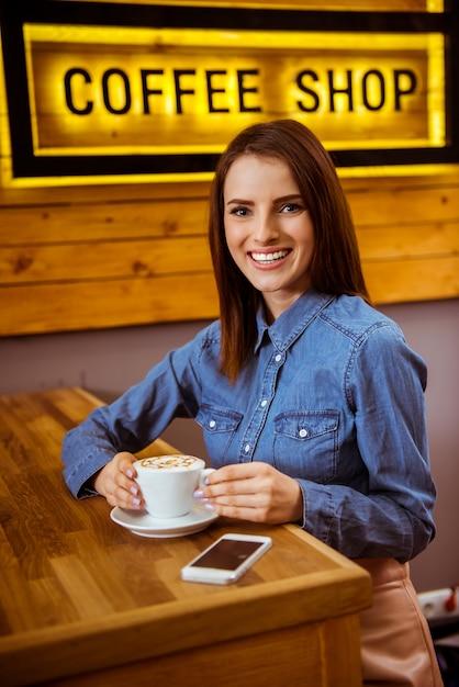 Une fille dans un bon café boit un délicieux café. Photo Premium