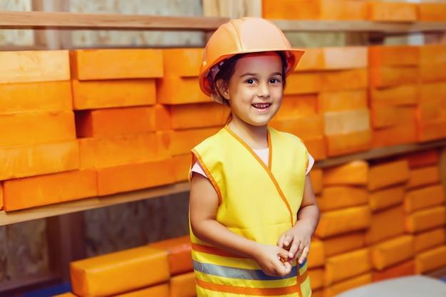 Une fille dans un casque sur le chantier de construction d'une maison à ossature en bois Photo Premium