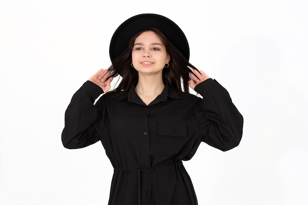 Une Fille Dans Un Chapeau Noir Pose Et Sourit Sur Fond Blanc Tenant Son Chapeau Photo Premium