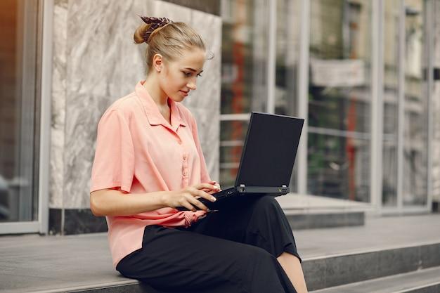Fille dans une chemise rose assis près de la maison et utilise l'ordinateur portable Photo gratuit