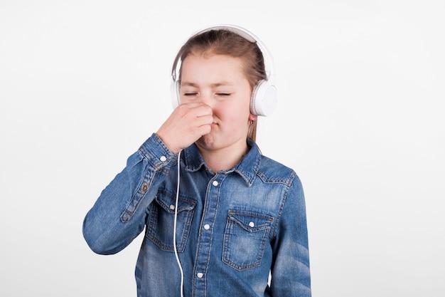 Fille dans les écouteurs couvrant le nez Photo gratuit