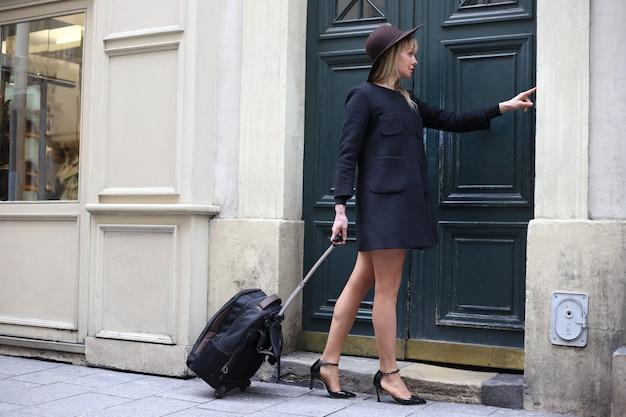 Une Fille Dans Un Manteau Court Noir Avec Chapeau Et Valise Sonne à La Porte Photo Premium