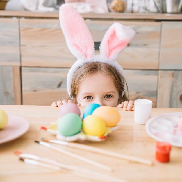 Fille dans des oreilles de lapin se cachant derrière une table avec des oeufs de pâques Photo gratuit
