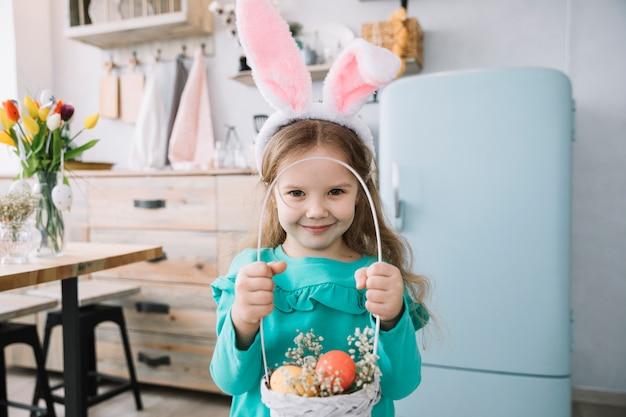 Fille dans des oreilles de lapin tenant un panier avec des oeufs de pâques Photo gratuit