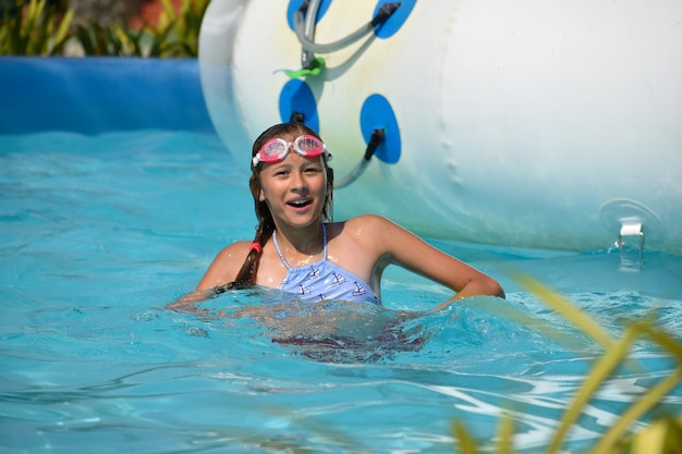 Fille Dans Le Parc Aquatique. S'amuser Sur L'eau. Photo Premium
