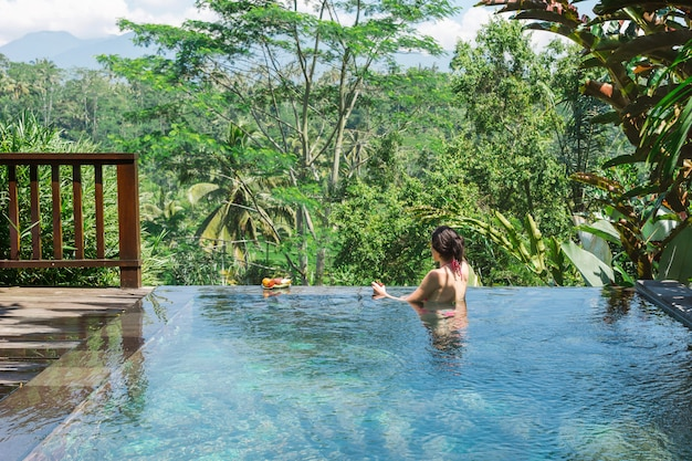 Fille dans une piscine privée à bali admire une vue magnifique sur les palmiers. Photo Premium