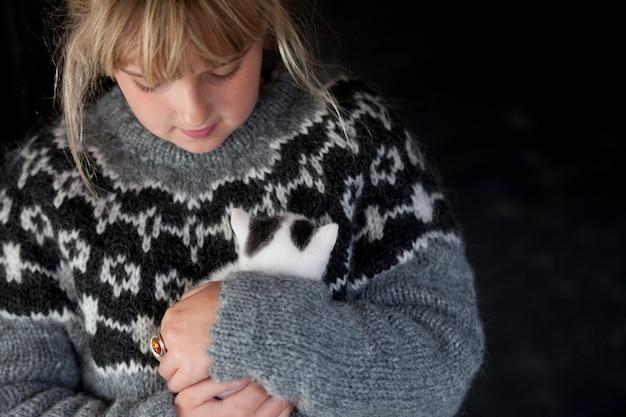 Fille Dans Un Pull Islandais En Tricot à La Main Tenant Une Banque Moelleuse Et Un Chaton Blanc En Islande Photo Premium