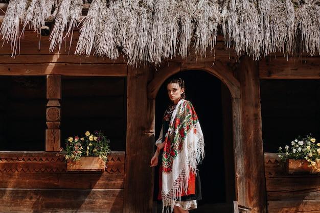 Fille dans la robe brodée ukrainienne pose près de la maison Photo gratuit