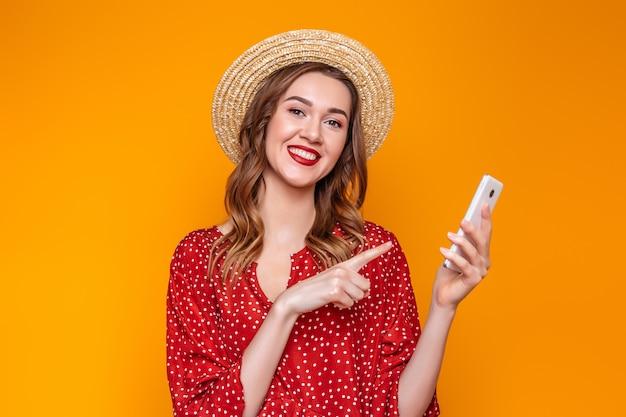 Fille Dans Une Robe, Un Chapeau De Paille Tient Un Téléphone Mobile Et Pointe Un Doigt Sur Lui Isolé Sur Fond Orange Photo Premium