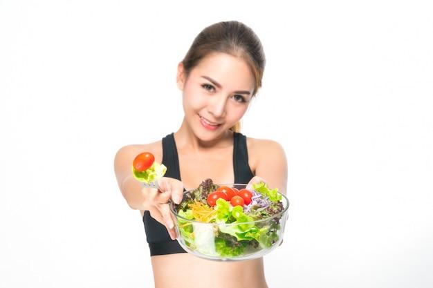 Fille dans une salle de fitness est titulaire d'un saladier. Photo Premium