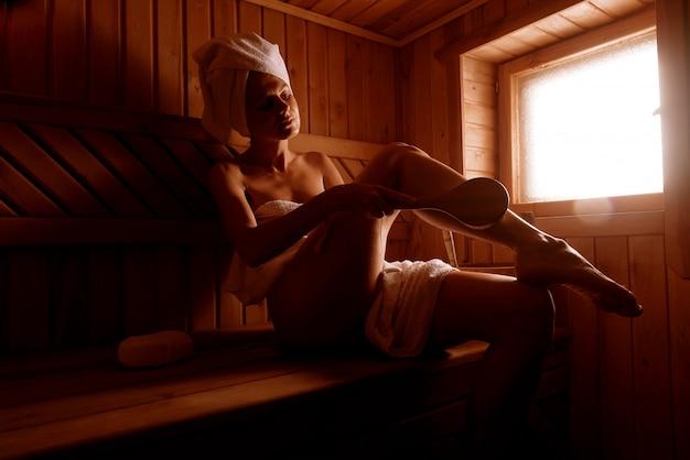 Fille Dans Un Traitement De Spa Dans Un Sauna Traditionnel Avec Une Brosse Pour La Peau Et Un Gant De Toilette. Photo Premium