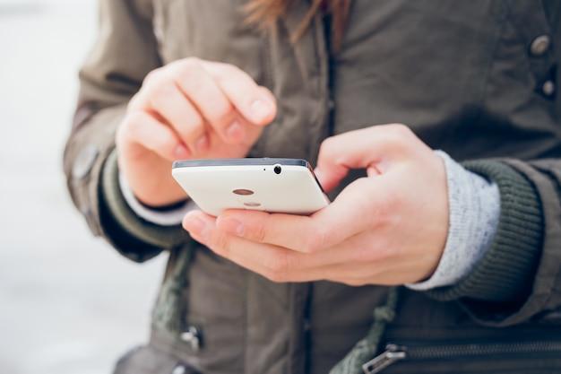 Fille Dans Une Veste Verte Utilise Un Smartphone Tout En Marchant Sur Le Fond De La Mer Photo Premium