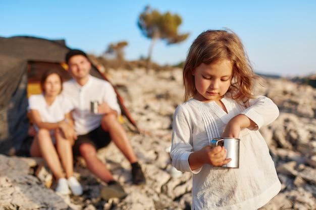Fille Debout Sur La Plage Et Mettant Sa Main Dans Une Tasse. Photo Premium