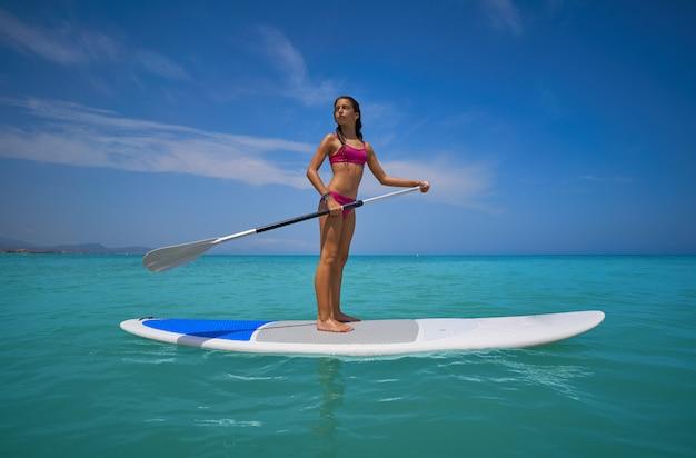 Fille debout sur une planche de surf paddle sup Photo Premium