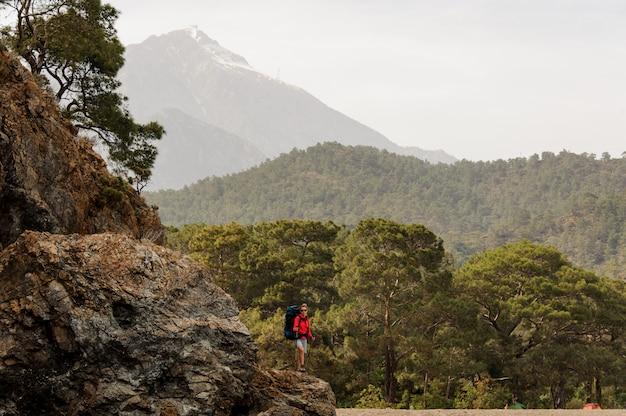 Fille debout sur le rocher avec sac à dos de randonnée et bâtons de marche Photo Premium