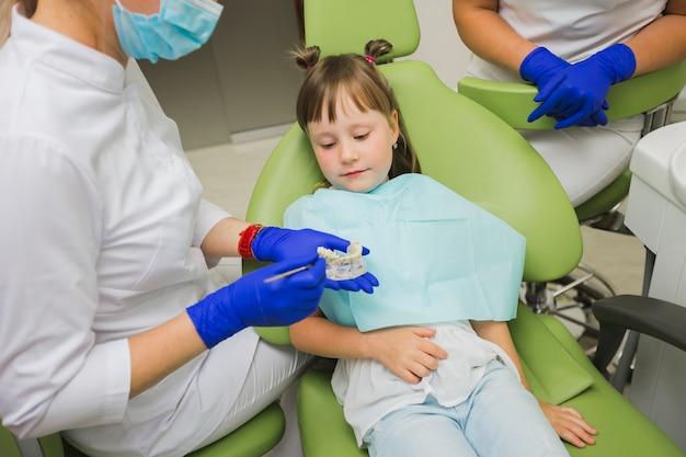 Fille, dentiste, regarder, dentiers Photo gratuit