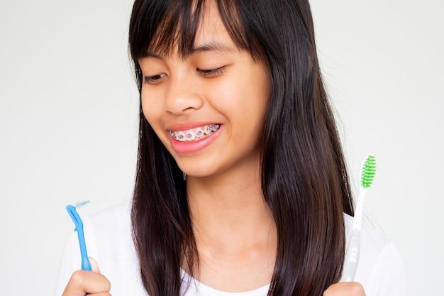 Fille avec des dents d'accolades main tenant la brosse à dents souriante et heureuse Photo Premium
