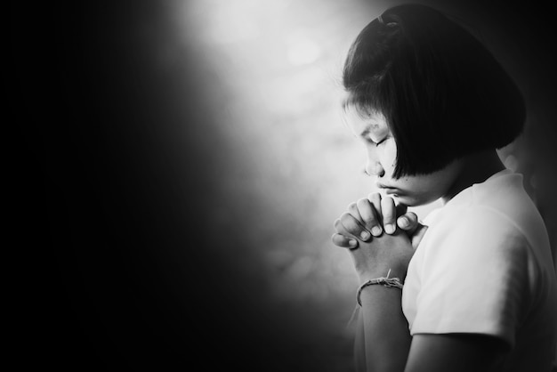 Fille déprimée et sans espoir priant dans le noir dans les tons blancs Photo Premium