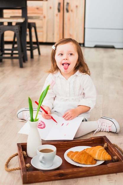 Fille dessiner et faire des grimaces près du plateau Photo gratuit