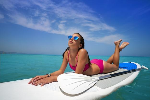 Fille détendue allongée sur une planche de surf paddle sup Photo Premium