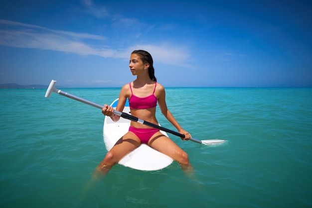 Fille détendue assise sur une planche de surf paddle sup Photo Premium