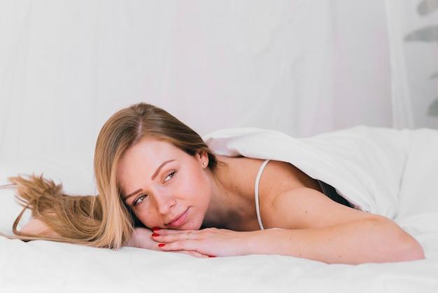 Fille détendue dans le lit Photo gratuit