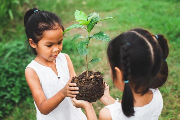 Fille de deux enfants tenant le jeune arbre pour la plantation ensemble comme concept de sauver le monde Photo Premium