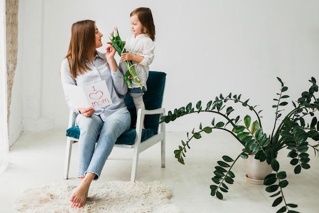 Fille Donnant Des Fleurs à La Mère Avec Carte De Voeux Photo gratuit