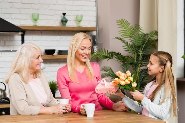 Fille Donnant à La Mère Un Bouquet De Fleurs Photo gratuit