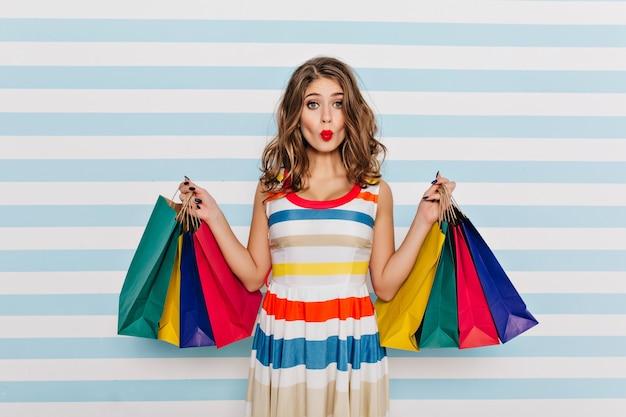 Fille Drôle En Robe Rayée Posant Avec L'expression Du Visage Embrassant Après Le Shopping. Glamour Jeune Femme Aux Cheveux Bouclés Tenant Des Sacs De Boutique. Photo gratuit