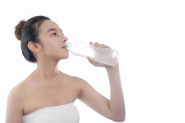 Fille de l'eau potable sur un fond blanc. Photo gratuit