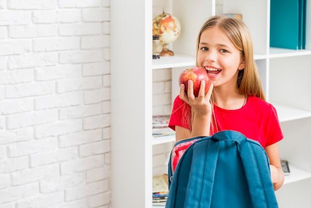 Fille d'école primaire ayant l'intention de mordre la pomme Photo gratuit