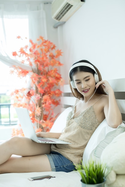 Fille avec des écouteurs écoutant de la musique dans un ordinateur portable sur le lit à la maison Photo gratuit