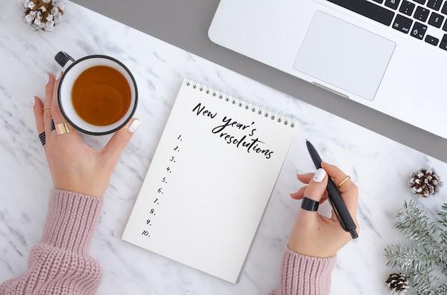Fille écrivant des résolutions du nouvel an. vue de dessus concept de noël et nouvel an Photo Premium