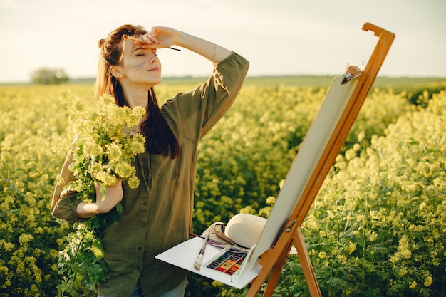 Fille élégante et belle peinture dans un champ Photo gratuit