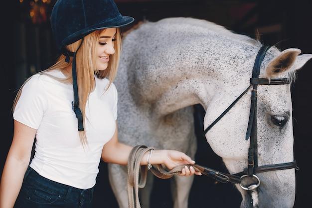 Fille élégante dans une ferme avec un cheval Photo gratuit