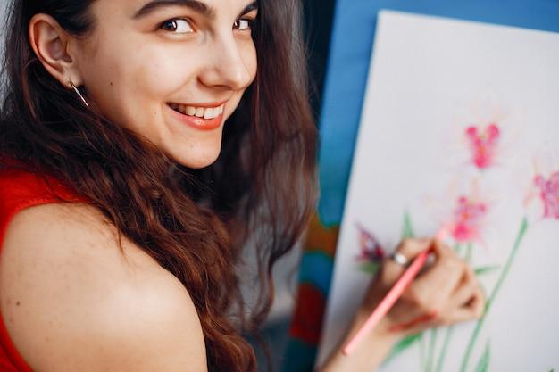 Fille élégante dessine dans un studio d'art Photo gratuit